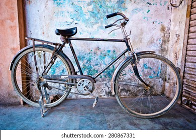 old bicycle leaning against vintage facade