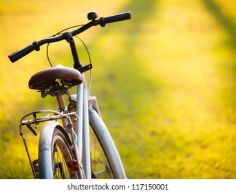 An old bicycle in meadow during sunset with shallow dept of field