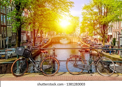 Old bicycle on the bridge in Amsterdam, Netherlands against a canal during summer sunny day. Amsterdam postcard iconic view. Tourism concept.