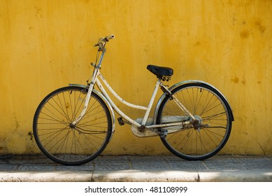 Old bicycle on yellow wall