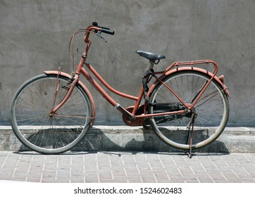 Old bicycle parked beside the wall