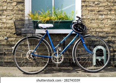 Old bicycle parked in front of a rustic cottage closeup