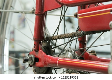 Old bicycle whell in red color with rusted chain. Light blurred background. Joinville, Santa Catarina, Brazil. 2015