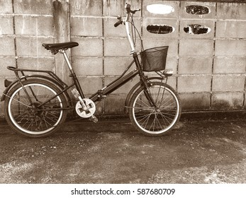 old Bicycle for women is beside a cement block fence.