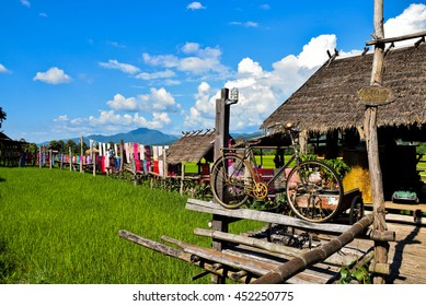 old bicycle and wood bridge  decorated with  Woven in native hut beside green farm in Nan, northern of Thailand, blue sky, blue sky cloud