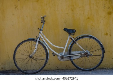 Old bicycle with yellow wall as background.