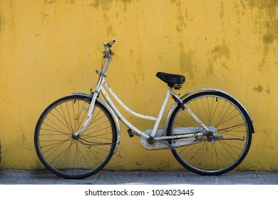 Old bicycle with yellow wall as background.Vietnam culture traditional,Hoi an,Life of Vietnamese