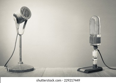 Old big retro microphones on table. Vintage style greyscale photo