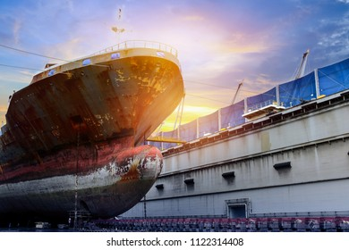 old big Ship repair with rusty in floating dock image of forward under wating for maintenance on sunset light in shipyard Thailand
