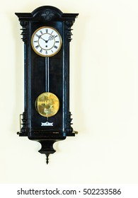 old big wooden pendulum clock hanging on wall