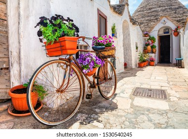 Old bike with flowers, Southern Italy. Beautiful street decorated with flowers in Italy.