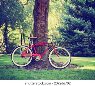 an old bike leaning against a big tree toned with a retro vintage instagram filter