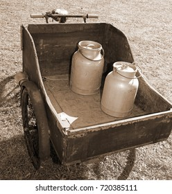 old bike with milk canister used once a long time ago from the milkman to deliver the fresh milk to the dairy with big wooden cart and sepia effect