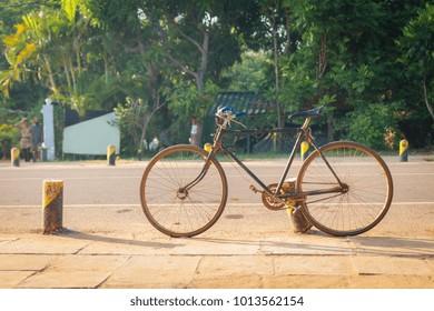 Old bike standing on the road, Sri Lanka