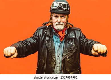 Old biker wearing leather jacket, hat and  sunglasses simulating to drive his motorcycle. - Concept of enjoying life at every age