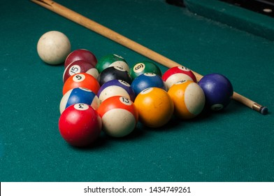 Old billiard ball and stick  on a green table. billiard balls isolated on a green background.