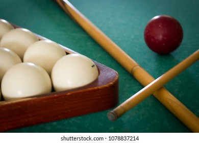 Old billiard balls on a table with green cloth