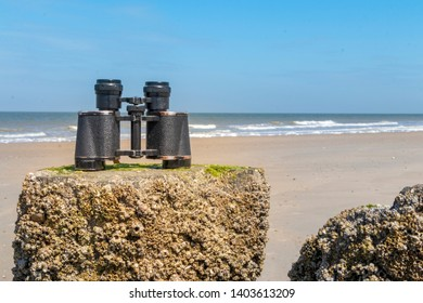 An old binocular is standing on a wooden plank at the beach. In the background the ocean and ble sky.