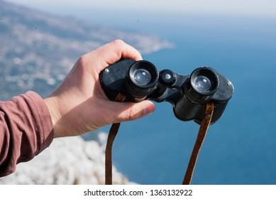 old binoculars in hand. view from the mountains to the sea
