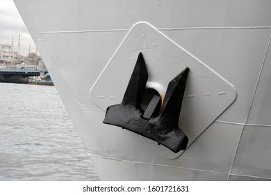 Old black anchor on the side of bow of white passenger ferry.
