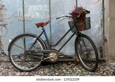 old black bicycle with flowers in the basket