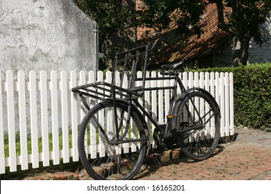 Old black bicycle standing against white picket fence in the Netherlands