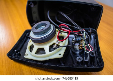 Old black broken speaker shows the magnet and circuit board and connection of wires