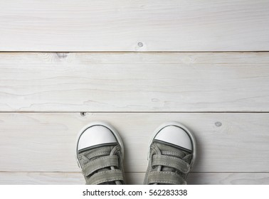 old black canvas shoes or sneakers in kids or baby foot stand on vintage white wood floor or table top view for keep walking with copyspace