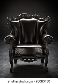 old black chair, upholstered in leather, isolated on a black background scratching.