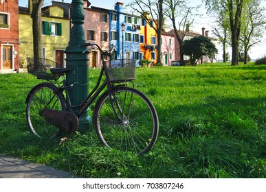 Old black city bicycle with basket chained to a pole in grass in front of colorful houses in Burano island in summer