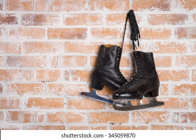Old Black Figure Ice Skates Hanging On A Brick Wall
