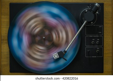 Old black gramophone during playing colorful vinyl plate. Creative close up product macro photography by using long time exposition.