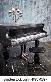 Old black grand piano with burning candles in candlestick at lid stands in room with ragged walls and floor.