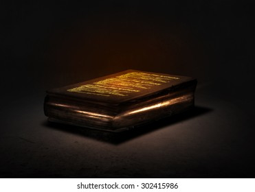 Old black magic book with lights on pages