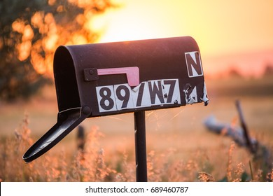 Old black mailbox with worn numbers in a bright, rural countryside setting.