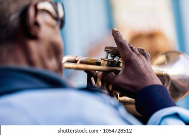 An old black man in blue jacket playing trumpet. Vinales in Cuba.
