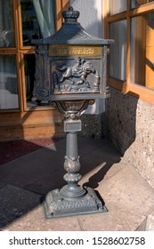 Old black metal mailbox on a metal base. The bas-relief is made on the box - the postman on a horse is blowing a horn. The mailbox and the base are richly decorated