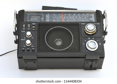 Old black multiband radio receiver with an external transverse antenna on the top panel, with two protruding chrome handles on the front panel, the speaker looks through the metal grille