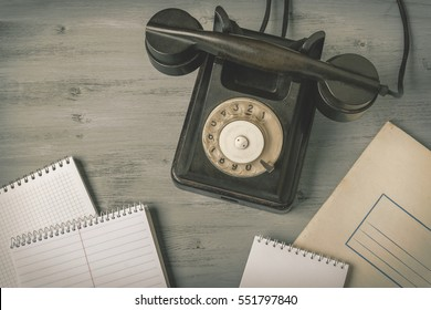 Old black phone and notepads on the table