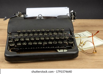 an old black portable typewriter with a steno pad and eye glasses as at a secretary's desk