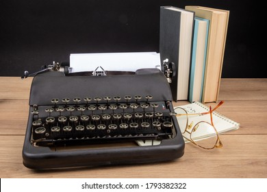 an old black portable typewriter with a steno pad and eye glasses and text books as at a secretary's desk