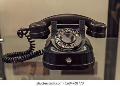 Old black rotary disk telephone with a handset on a spring cable.