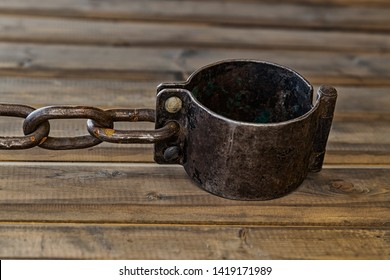 old black shackled shackles with a chain lie on a wooden bench a symbol of slavery and oppression