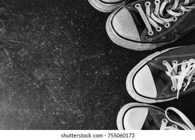 Old black sneakers and on a dark marble background. Footwear for outdoor activities. Black and white art monochrome photography.