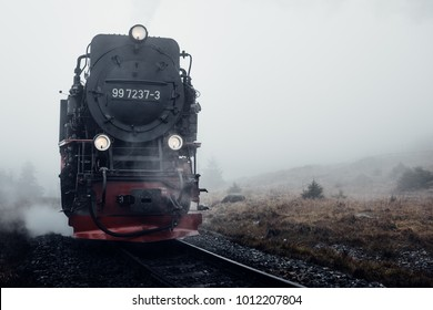 Old black steam locomotive comes out of the fog