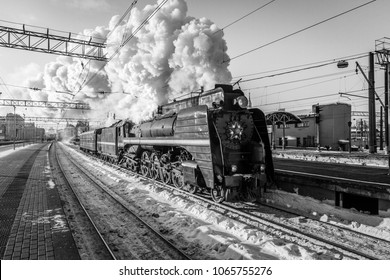 old black steam locomotive in Russia in the winter and electric trains on the background of the Moscow railway station.