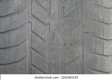 Old black tire with worn tread and cracks, worn old car tire tread, old damaged, worn black tire tread, large cracks in the car wheel, tire black color for background.
