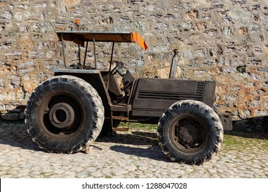old black tracktor on backround rock wall