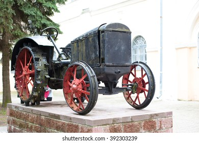 An old black tractor as a monument