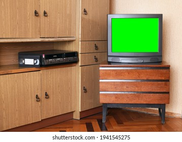 An old black TV with a green screen to add video and a VCR against old furniture from the 1980s and 1990s.Design in the house in the style of the 1980s and 1990s.
